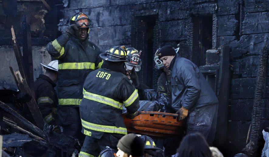 Firefighters carry the body of a victim from a burned three-story, single-family house Sunday, Dec. 7, 2014, in East Orange, N.J. Four people, ranging in age from six weeks to 78 years, were killed in an early morning fire at the house. (AP Photo/Mel Evans)