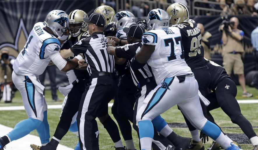 Officials separate players during a scuffle after a touchdown by the Carolina Panthers in the first half of an NFL football game against the New Orleans Saints in New Orleans, Sunday, Dec. 7, 2014. (AP Photo/Bill Feig)