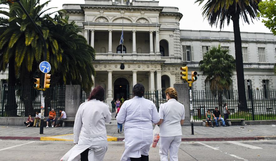 Three doctors enter the military hospital in Montevideo, Uruguay, Sunday, Dec. 7, 2014. Six prisoners from Guantanamo Bay have been transferred to Uruguay, the U.S. government said Sunday. Uruguayan officials declined comment on the transfers but Adriana Ramos, a receptionist at the hospital, said the six men were being examined there. (AP Photo/Matilde Campodonico)