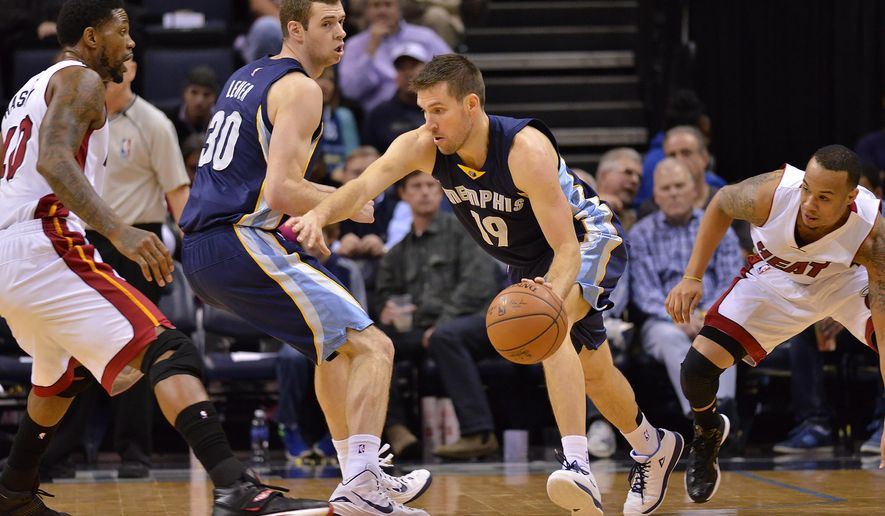 Memphis Grizzlies guard Beno Udrih (19) drives between Miami Heat forward Udonis Haslem (40), Jon Leuer (30) and Shabazz Napier (13) in the first half of an NBA basketball game Sunday, Dec. 7, 2014, in Memphis, Tenn. (AP Photo/Brandon Dill)