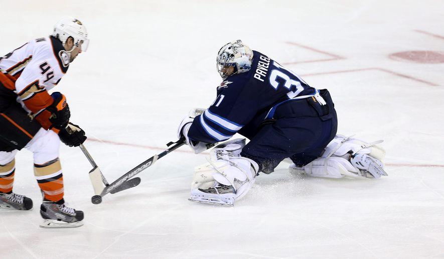 Winnipeg Jets goaltender Ondrej Pavelec (31) comes way out of the net to poke check Anaheim Ducks' Nate Thompson (44) during third period NHL hockey action in Winnipeg, Manitoba, Sunday, Dec. 7, 2014. (AP Photo/The Canadian Press, Trevor Hagan)
