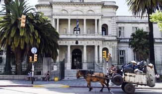 A horse cart passes by the military hospital in Montevideo, Uruguay, Sunday, Dec. 7, 2014.  Six prisoners from Guantanamo Bay have been transferred to Uruguay, the U.S. government said Sunday. Uruguayan officials declined comment  on the transfers but Adriana Ramos, a receptionist at the hospital, said the six men were being examined there. (AP Photo/Matilde Campodonico)