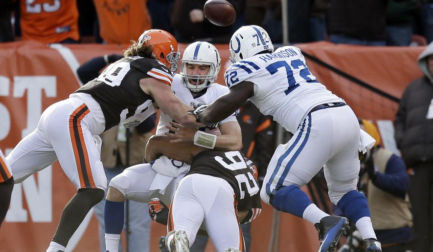 Indianapolis Colts quarterback Andrew Luck, center, fumbles the ball against Cleveland Browns outside linebacker Paul Kruger (99) in the first quarter of an NFL football game Sunday, Dec. 7, 2014, in Cleveland. The Browns recovered in the end zone for a touchdown. (AP Photo/Tony Dejak)