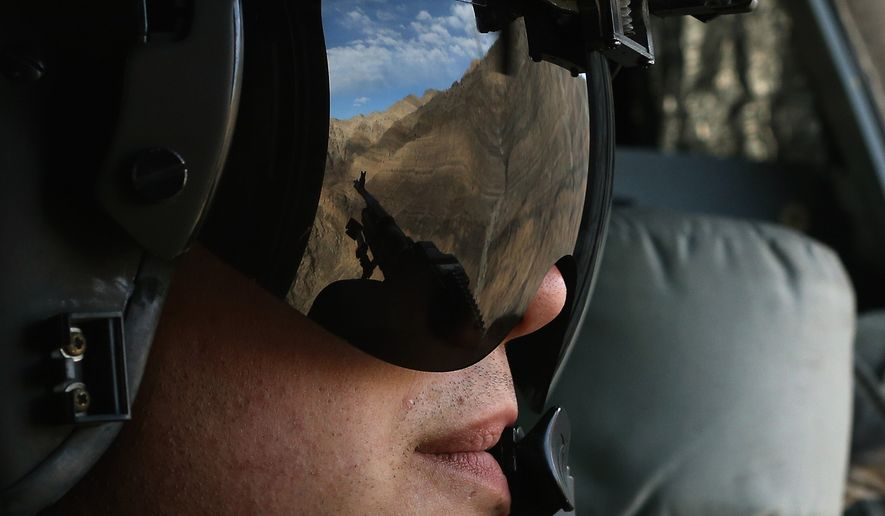 A US Army window gunner holds his weapon on a helicopter carrying U.S. Secretary of Defense Chuck Hagel during his visit to American troops in eastern Afghanistan, Sunday, Dec. 7, 2014. (AP Photo/Mark Wilson, Pool)
