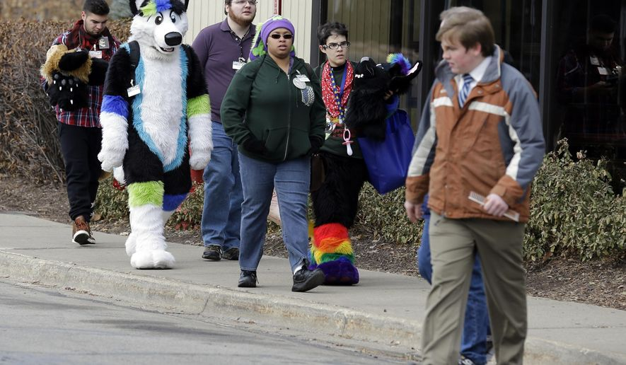 People walk on the street outside of the Hyatt Regency O'Hare in Rosemont, Ill., on Sunday, Dec. 7, 2014, in Rosemont, Ill. Thousands of people were evacuated after an chlorine gas leak at the Hyatt hotel hosting the 2014 Midwest FurFest convention, where attendees dress as animals to celebrate art, literature and performance, in suburban Rosemont early Sunday morning. Investigators believe the leak at the hotel in Rosemont was caused intentionally and are treating it as a criminal matter. (AP Photo/Nam Y. Huh)