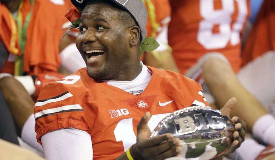 Ohio State quarterback Cardale Jones holds the championship trophy following the Big Ten Conference championship NCAA college football game against Wisconsin after midnight Sunday, Dec. 7, 2014, in Indianapolis. Ohio State won 59-0. (AP Photo/Michael Conroy)