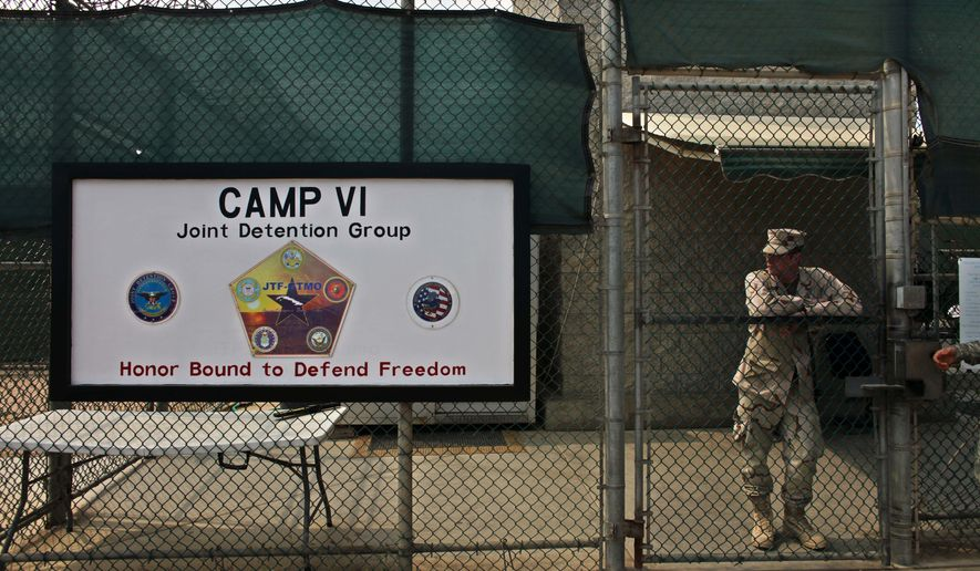 FILE - In this file photo taken Tuesday May 12, 2009 and  reviewed by the U.S. military, a soldier stands guard at the front gate entrance to Guantanamo's Camp 6 maximum-security detention facility, at Guantanamo Bay U.S. Naval Base, Cuba. The U.S. government said Sunday Dec. 7, 2014 six men who have been held more than 12 years at Guantanamo Bay have been sent to Uruguay to be resettled as refugees. (AP Photo/Brennan Linsley, File)