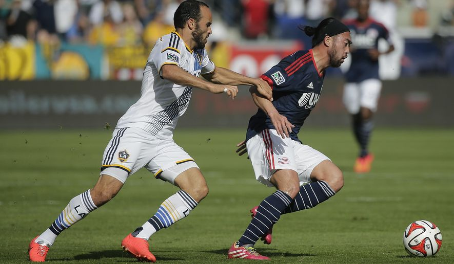 Los Angeles Galaxy's Landon Donovan, left, grabs the arm of New England Revolution's Lee Nguyen during the first half of the MLS Cup championship soccer match Sunday, Dec. 7, 2014, in Carson, Calif. (AP Photo/Jae C. Hong)