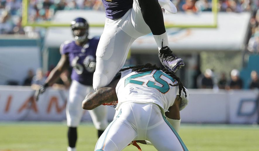 Baltimore Ravens wide receiver Marlon Brown (14) jumps over Miami Dolphins free safety Louis Delmas (25) during the second half of an NFL football game, Sunday, Dec. 7, 2014, in Miami Gardens, Fla. (AP Photo/Lynne Sladky)