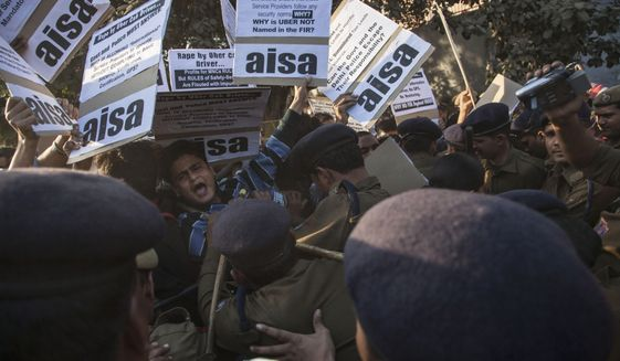 Police push away protestors from All India Students Association (AISA) who demonstrate outside the Delhi Police headquarters after a taxi driver from the international cab-booking service Uber allegedly raped a young woman Friday in New Delhi, India, Sunday, Dec. 7, 2014. Official statistics say about 25,000 rapes are committed every year in India, a nation of 1.2 billion people..(AP Photo/Tsering Topgyal)