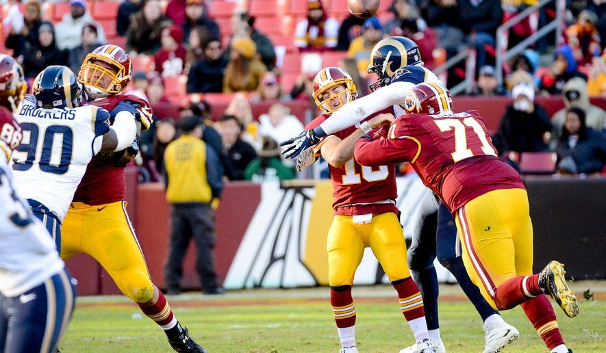 Washington Redskins quarterback Colt McCoy (16) is hit as he throws in the third quarter as the Washington Redskins play the St. Louis Rams in NFL football at FedExField, Landover, Md., Sunday, December 7, 2014. (Andrew Harnik/The Washington Times)