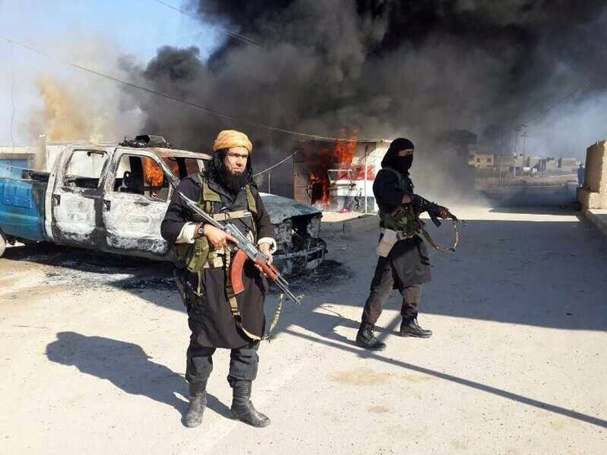 This undated file image posted on a militant website on Jan. 4, 2014, which is consistent with other AP reporting, shows Shakir Waheib, a senior member of the Islamic State of Iraq and the Levant (ISIL), now called the Islamic State group, left, next to a burning police vehicle in Iraq's Anbar Province. (AP Photo via militant website, File)