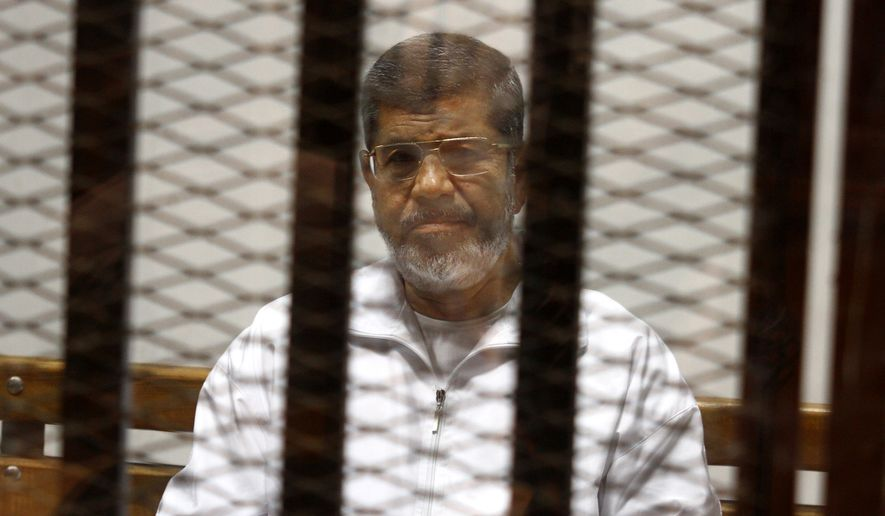 Egypt's ousted Islamist President Mohammed Morsi sits in a defendant cage in the Police Academy courthouse in Cairo, Egypt, in this May 8, 2014, file photo. (AP Photo/Tarek el-Gabbas, File)