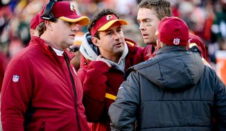 Washington Redskins head coach Jay Gruden listens as Washington Redskins quarterback Colt McCoy (16) talks to training staff members after coming out of the game late in the fourth quarter as the Washington Redskins play the St. Louis Rams in NFL football at FedExField, Landover, Md., Sunday, December 7, 2014. (Andrew Harnik/The Washington Times)