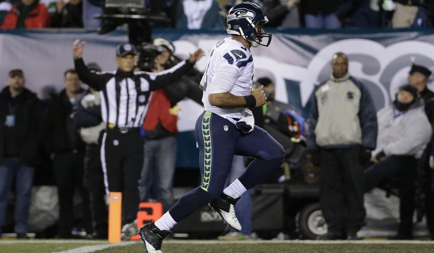Seattle Seahawks' Russell Wilson scores a touchdown during the first half of an NFL football game against the Philadelphia Eagles, Sunday, Dec. 7, 2014, in Philadelphia. (AP Photo/Michael Perez)