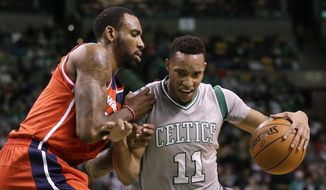 Boston Celtics guard Evan Turner, right, tries to drive past Washington Wizards forward Rasual Butler, left, in the second quarter of an NBA basketball game, Sunday, Dec. 7, 2014, in Boston. (AP Photo/Steven Senne)