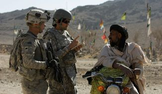 interpreter: U.S. Army Sgt. Skyler Rosenberry of Pennsylvania (left) and an interpreter speak to an Afghan man in a village in Afghanistan. U.S. visas are often awarded to Afghan translators in gratitude for their help in anti-Taliban efforts. (Associated Press)