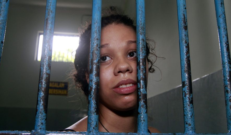 American Heather Mack looks out from a cell at the Indonesian prosecutor's office as the police handed her murder case to the prosecutor in Bali, Indonesia, Monday, Dec. 8, 2014. Mack and her boyfriend Tommy Schaefer are accused of murdering Sheila von Wiese-Mack, her mother, who was found stuffed inside a suitcase last August. (AP Photo/Firdia Lisnawati)