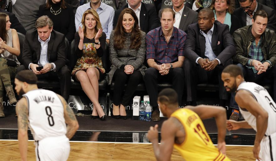 Britain's Prince William, third from right, and Kate, Duchess of Cambridge, sit with former Houston Rockets player Dikembe Mutombo, second from right, during the second half of an NBA basketball game between the Brooklyn Nets and the Cleveland Cavaliers, Monday, Dec. 8, 2014, in New York. (AP Photo/Frank Franklin II)