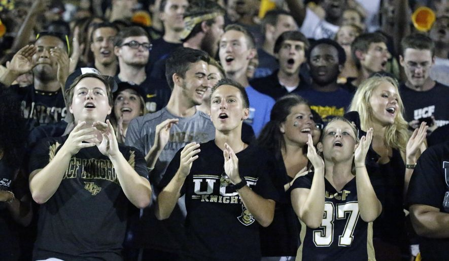 In this Thursday, Oct. 9, 2014 photo, University of Central Florida students cheer during an NCAA college football game against Brigham Young in Orlando, Fla. Florida's public universities are continuing to rely on some of the highest student athletic fees in the nation.(AP Photo/John Raoux)