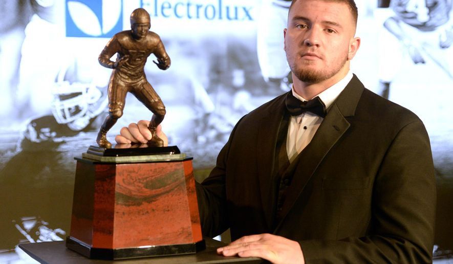 Arizona linebacker Scooby Wright, finalist for the Bronko Nagurski Trophy, poses with the trophy in Charlotte, N.C., Monday, Dec. 8, 2014.  The award is presented by the Charlotte Touchdown Club, as voted on by the Football Writers Association of America, to college football's top defensive player. (AP Photo/The Charlotte Observer, David T. Foster. III) MAGS OUT; TV OUT; NEWSPAPER INTERNET ONLY