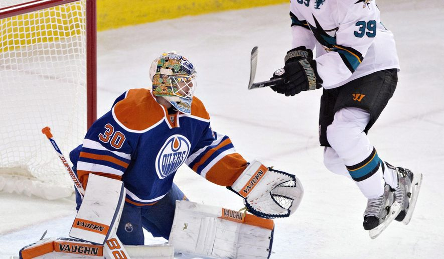 San Jose Sharks' Logan Couture (39) tries to screen Edmonton Oilers goalie Ben Scrivens (30) during third period of an NHL hockey game in Edmonton, Alberta, Sunday, Dec. 7, 2014. (AP Photo/The Canadian Press, Jason Franson)