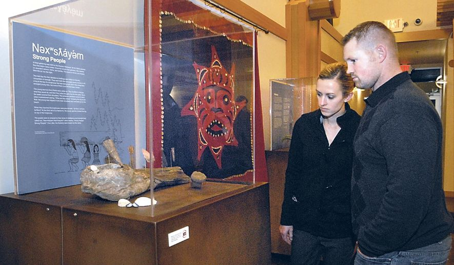 In this Thursday, Dec. 4, 2014 photo, Jessica and Mike Tade, of Sequim, Wash., look at a display of Lower Elwha Klallam artifacts during the first public showing of the artifacts at the Elwha Heritage Center in Port Angeles, Wash. Seven from a collection of a thousand etched stones, once buried below the place that became Port Angeles and which tell the story of the Klallam people, are displayed alongside some two dozen other artifacts. They came to light when the ancient Klallam village of Tse-whit-zen was discovered in 2003. (AP Photo/Peninsula Daily News, Keith Thorpe)