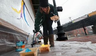 In this Wednesday, Nov. 25, 2014 photo, Darcy Edwin of Ferguson dabs paint on a brush as she begins a mural on the boards protecting Ferguson Optical on S. Florissant Road in downtown Ferguson, Mo. The Missouri History Museum and the Regional Art Commission are working to preserve art that sprung up on plywood meant to protect storefronts or cover damage from protesting in Ferguson and St. Louis. (AP Photo/St. Louis Post-Dispatch, Christian Gooden)  EDWARDSVILLE INTELLIGENCER OUT; THE ALTON TELEGRAPH OUT