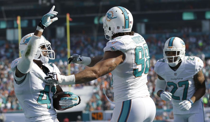 Miami Dolphins defensive back R.J. Stanford (41) is congratulated by tackle Jared Odrick (98) and strong safety Jimmy Wilson (27) after Stanford intercepted the ball in the end zone during the first half of an NFL football game against the Baltimore Ravens, Sunday, Dec. 7, 2014, in Miami Gardens, Fla. (AP Photo/Wilfredo Lee)