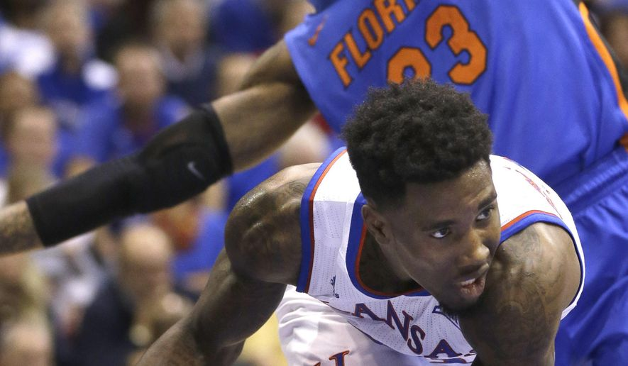 Kansas forward Jamari Traylor (31) is fouled by Florida forward Chris Walker (23) during the first half of an NCAA college basketball game in Lawrence, Kan., Friday, Dec. 5, 2014. (AP Photo/Orlin Wagner)