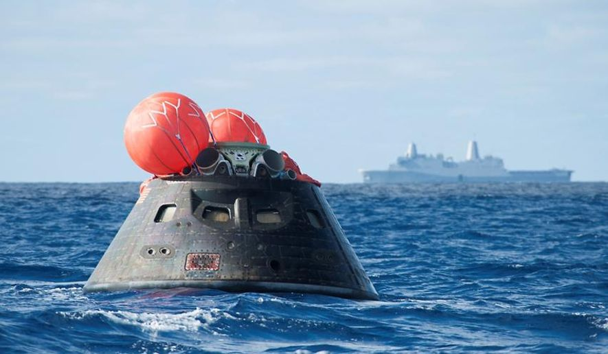 This Dec. 5, 2014 image provided by NASA shows NASA's Orion spacecraft after splash down as it awaits the U.S. Navy's USS Anchorage in the Pacific ocean.  Orion launched into space on a two-orbit, 4.5-test flight at 7:05 am EST on Dec. 5, and safely splashed down in the Pacific Ocean, where a combined team from NASA, the Navy and Orion prime contractor Lockheed Martin retrieved it for return to shore on board the Anchorage. It is expected to be off loaded at Naval Base San Diego on Monday.  (AP Photo/NASA)