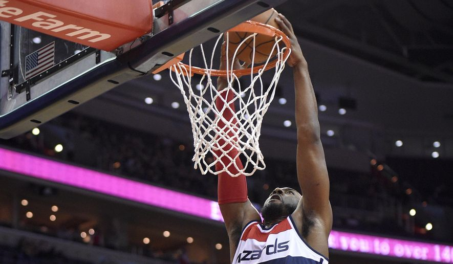 Washington Wizards guard John Wall (2) dunks over Boston Celtics guard Rajon Rondo, bottom right, during the first half of an NBA basketball game, Monday, Dec. 8, 2014, in Washington. (AP Photo/Nick Wass)
