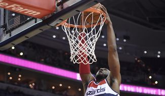 Washington Wizards guard John Wall (2) dunks over Boston Celtics guard Rajon Rondo, bottom right, during the first half of an NBA basketball game, Monday, Dec. 8, 2014, in Washington. (AP Photo/Nick Wass)