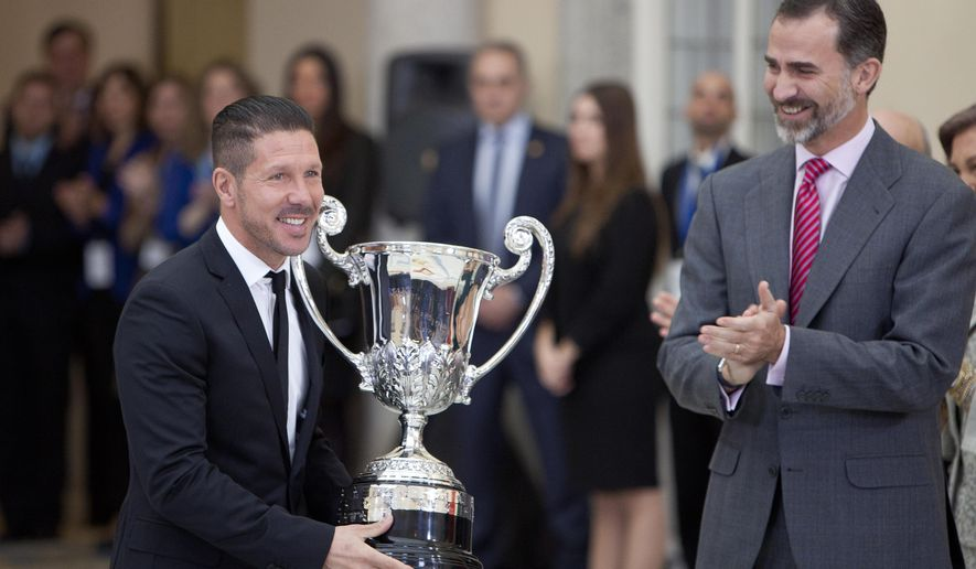 Atletico de Madrid's Argentine soccer coach Diego Pablo Simeone, left, poses after receiving the 'Ibero-American Community Trophy' from Spanish King Felipe VI, right during the 2013 Spanish National Sports Awards at El Pardo Palace in Madrid, on Thursday Dec. 4, 2014. (AP Photo/Abraham Caro Marin)