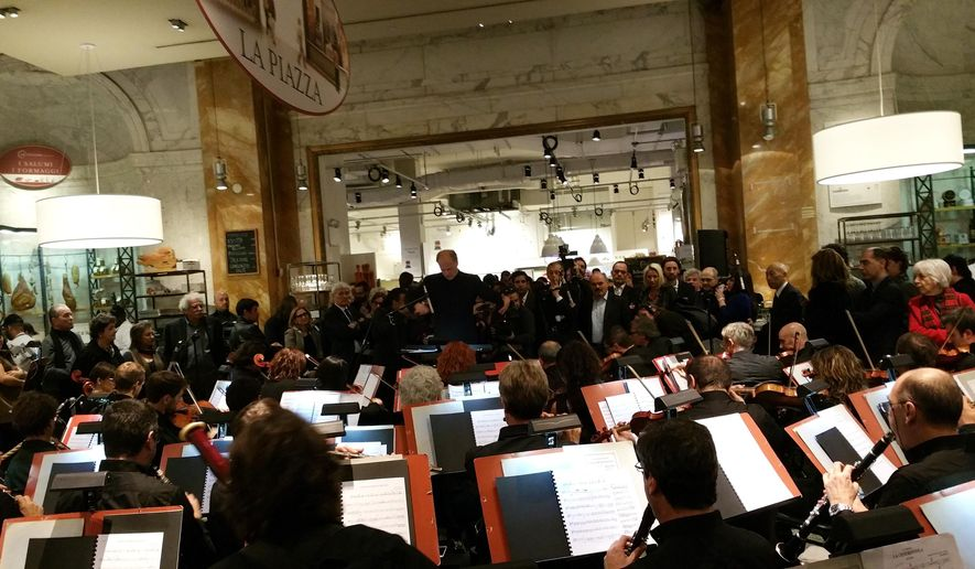 A world-class Italian orchestra served up the sounds of the season _ amid the pizza, pasta and pepperoni of a Manhattan food emporium. The orchestra and chorus of the Teatro Regio from Turin played Sunday, Dec. 7, 2014, at Eataly, in New York City. The event benefited the Geneva-based Global Fund to Fight AIDS, Tuberculosis, and Malaria.(AP Photo/ Verena Dobnik)