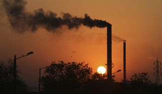 Birds fly past at sun set as smoke emits from a chimney at a factory in Ahmadabad, India, Monday, Dec. 8, 2014. The momentum from a historic U.S.-China pact to resist global warming is showing signs of fading at the U.N. climate talks in Peru as the familiar rich-poor conflict persists over who should do what to keep the planet from overheating. The conference's high-level phase begins Tuesday. (AP Photo/Ajit Solanki)