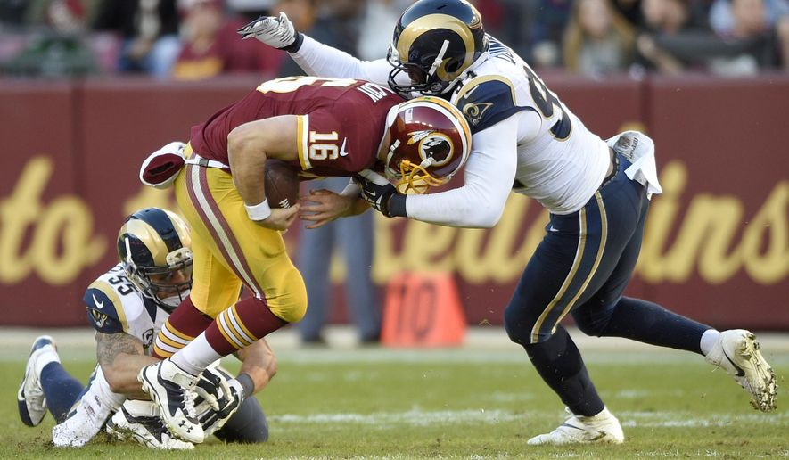 Washington Redskins quarterback Colt McCoy (16) is sacked by St. Louis Rams middle linebacker James Laurinaitis (55) and defensive end Robert Quinn (94) during the second half of an NFL football game in Landover, Md., Sunday, Dec. 7, 2014. The Rams defeated the Redskins 24-0. (AP Photo/Nick Wass)