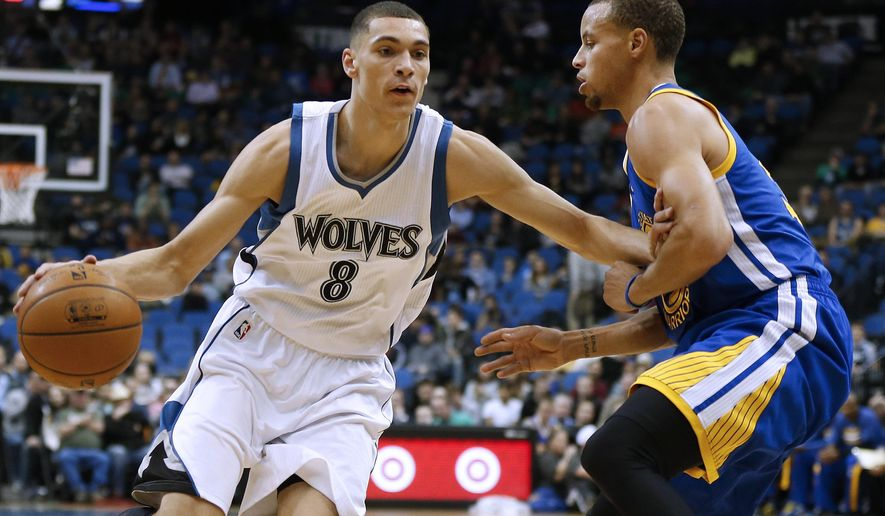 Minnesota Timberwolves guard Zach LaVine (8) pushes the ball down the court past Golden State Warriors guard Stephen Curry (30) during the first half of an NBA basketball game Monday, Dec, 8, 2014, in Minneapolis. (AP Photo/Stacy Bengs)