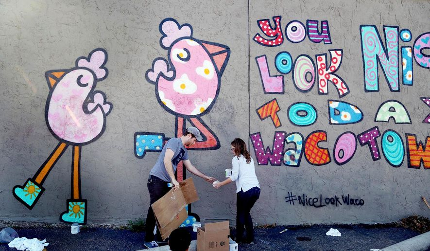In this Saturday, Dec. 6, 2014 photo, volunteers Andy Anzollitto, left, and Katie Wolfe touch up the mural painted last spring by British street artist Binty Bint, on a wall in downtown Waco, Texas. Waco police on Saturday said two teenagers have been charged with using spray paint to deface the mural. (AP Photo/Waco Tribune Herald, Rod Aydelotte)
