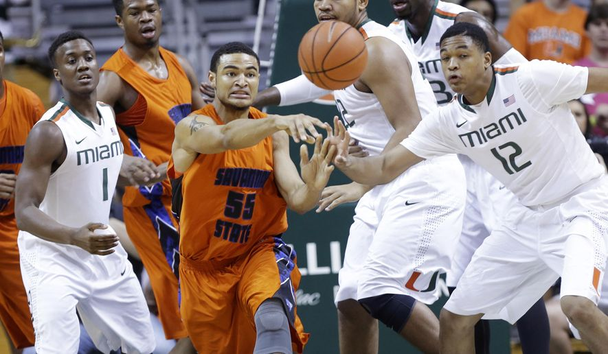Savannah State forward Brian Pearson (55) passes the ball as Miami guard Deandre Burnett (1) and guard James Palmer (12) defend in the first half of an NCAA college basketball game, Monday, Dec. 8, 2014, in Coral Gables, Fla. (AP Photo/Lynne Sladky)