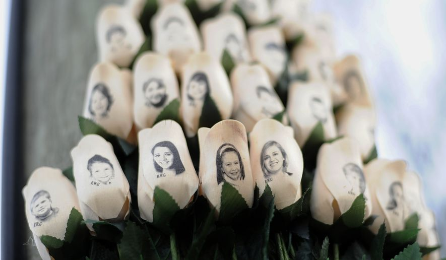 FILE - In this Jan. 14, 2013 file photo, white roses with the faces of victims of the Sandy Hook Elementary School shooting are attached to a telephone pole near the school on the one-month anniversary of the shooting that left 26 dead in Newtown, Conn. Newtown is taking its time to decide what a permanent memorial should look like. A commission has been hearing proposals for concepts including murals, groves and memorial parks, while looking for lessons from paths chosen by other tragedy-stricken communities. Public forums are planned for 2015, the next step in a process that is expected to last several more years. (AP Photo/Jessica Hill, File)