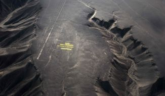 "Greenpeace activists stand next to massive letters delivering the message ""Time for Change: The Future is Renewable,"" next to the hummingbird geoglyph in Nazca in Peru, Monday, Dec. 8, 2014. Greenpeace activists from Brazil, Argentina, Chile, Spain, Germany, Italy and Austria displayed the message, which can be viewed from the sky, during the climate talks in Peru, to honor the Nazca people, whose ancient geoglyphs are one of the country's cultural landmarks. (AP Photo/Rodrigo Abd)"