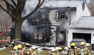 Firefighters stand outside a house in Gaithersbug, Md., Monday, Dec. 8, 2014, where a small plane crashed. A small, private jet has crashed into a house in Maryland's Montgomery County, and a fire official says at least three people on board were killed. (AP Photo/Jose Luis Magana)