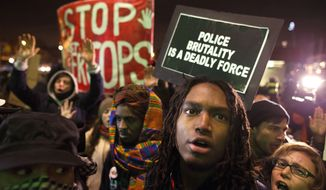 Protestors rally outside the Barclays Center against a grand jury's decision not to indict the police officer involved in the death of Eric Garner, Monday, Dec. 8, 2014, in the Brooklyn borough of New York. (AP Photo/John Minchillo)