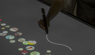 "This photo provided by Cooper Hewitt, Smithsonian Design Museum shows the Rendering of the Pen in use on the interactive tables and the ""digital river"" of collection objects. The concept, design, and production is by Local Projects LLC.  The Cooper-Hewitt Smithsonian Design Museum, revamped, restored and seriously expanded after a three-year closure, is reopening at last, all decked out for the 21st century within its historic Carnegie Mansion home. It opens to visitors Friday, Dec. 12, 2014.  (AP Photo/Cooper Hewitt, Smithsonian Design Museum)"