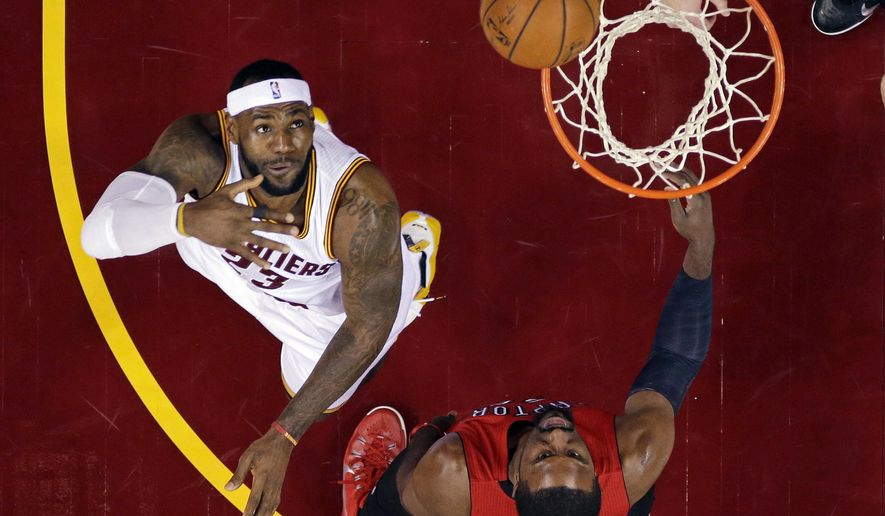 Cleveland Cavaliers' LeBron James, left, flips up a shot over Toronto Raptors' Patrick Patterson in the first half of an NBA basketball game Tuesday, Dec. 9, 2014, in Cleveland. (AP Photo/Mark Duncan)