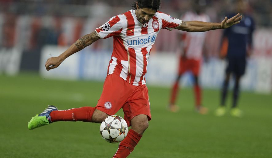 Olympiakos' Alejandro Damian Dominguez scores his side's second goal during the Champions League Group A soccer match between Olympiakos and Malmo at Georgios Karaiskakis Stadium in the port of Piraeus near Athens, Tuesday, Dec. 9, 2014. (AP Photo/Thanassis Stavrakis)