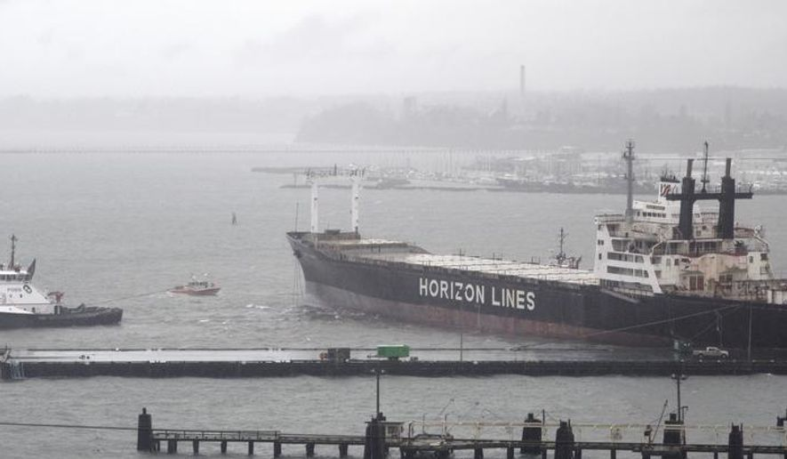 The Garth Foss tugboat pulls the Horizon freighter back to the Bellingham Shipping Terminal after it broke loose during high winds Tuesday,  Dec. 9, 2014, in Bellingham, Wash.  The ship is used to carry containers to Alaska but is not currently active and carries no fuel.  (AP Photo/The Bellingham Herald, Philip A. Dwyer)