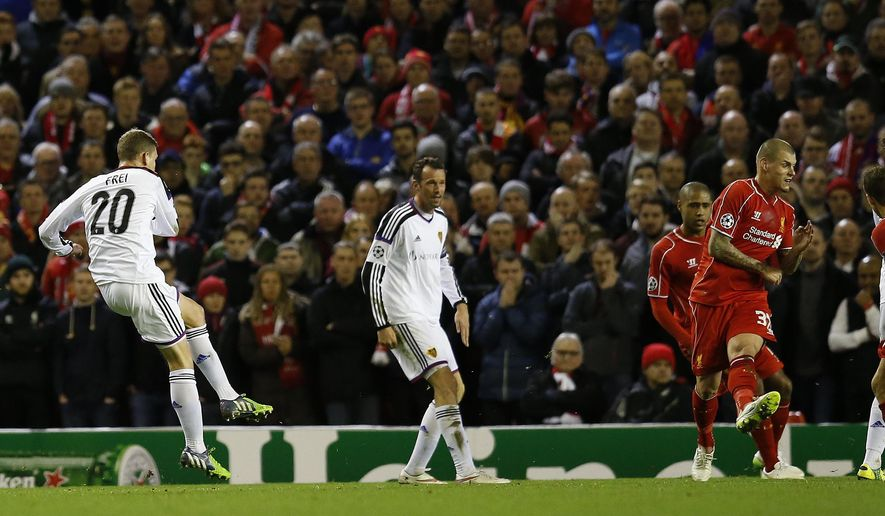 Basel's Fabian Frei, left, follows through after scoring the opening goal during the Champions League Group B soccer match between Liverpool and FC Basel at Anfield Stadium in Liverpool, England, Tuesday, Dec. 9, 2014. (AP Photo/Jon Super)