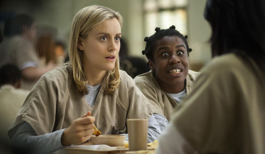 """FILE - This image released by Netflix shows Taylor Schilling, left, and Uzo Aduba in a scene from """"Orange Is the New Black."""" Saginaw Valley State University Assistant Professor of English Kim Lacey is teaching a course, Writing about Oppression on TV, centering on """"Orange Is the New Black,"""" in the winter 2015 semester, The Saginaw News reported. (AP Photo/Netflix, Paul Schiraldi, File)"""
